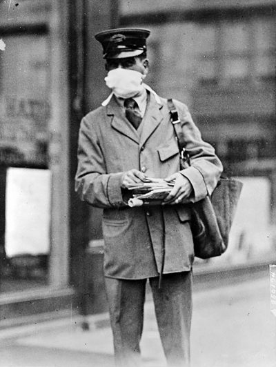 pandemics-Letter carrier in New York wearing mask for protection against influenza